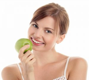 lady smiling with apple in hand